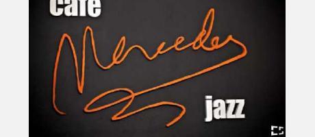 Logotipo del Café Mercedes sobre fondo negro en letras naranja y blanco