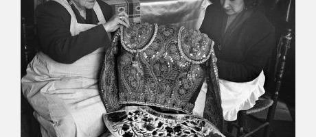 Fotografía en blanco y negro de dos mujeres tejiendo un traje de luces.