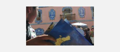 un niño sostiene el folleto turístico de Manises y al fondo se ve El Arte