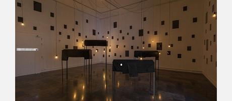 Cartel de la exposición, donde podemos ver unas mesas y unas lámparas colgadas